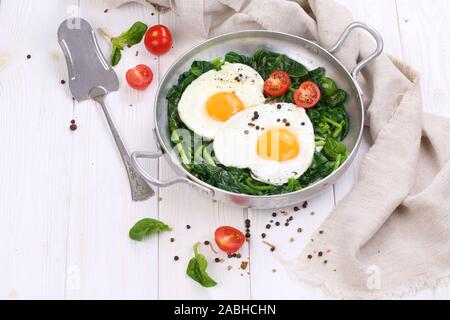 Fried eggs with spinach and tomatoes on a white, wooden background - Stock Photo