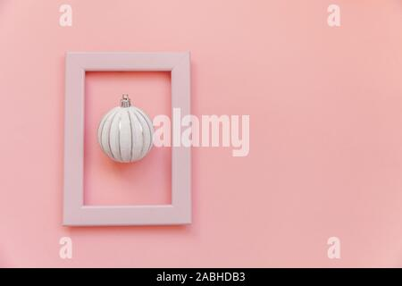 Simply minimal composition winter objects ornament ball in pink frame isolated on pink pastel trendy background. Christmas New Year december time for celebration concept. Flat lay top view - Stock Photo