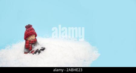 Christmas elf toy sits in the snow, banner for website header - Stock Photo