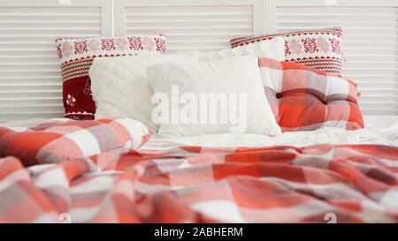 Winter Christmas decorations. Red White pillows on the bed.