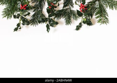 Christmas floral frame, web banner. Border of red holly berries and green fir tree branches isolated on white table background. Winter natural - Stock Photo