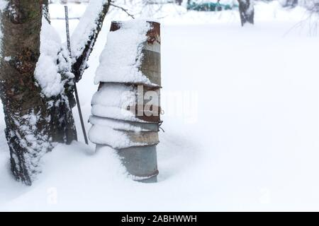 Winter rural landscape, rusty metal buckets in the yard covered with snow. - Stock Photo