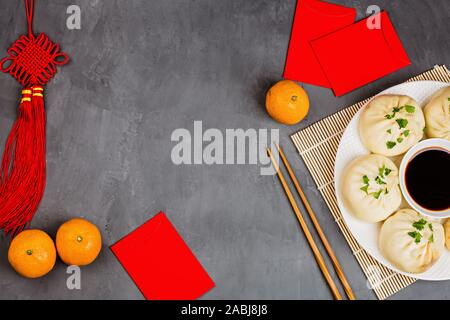 Chinese New Year decoration with dumplings, tangerines, soy sauce, chopsticks, red envelopes on gray background. Template. Happy Chinese new year 2020 - Stock Photo
