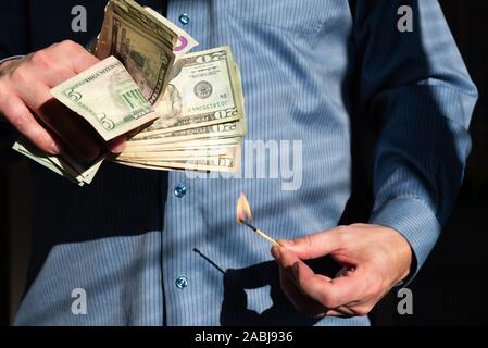 Close-up of man holding burning match near large handful of American dollars - Stock Photo