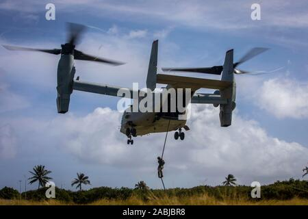 A U.S. Marine with 2nd Battalion, 3d Marine Regiment, fast ropes from a MV-22B Osprey assigned to Marine Medium Tiltrotor Squadron 363 during fast roping drills, Marine Corps Base Hawaii, Nov. 26, 2019. The training was designed to produce readiness by building confidence, familiarize the Marines with air assets, and prepare them for crisis response operations. (U.S. Marine Corps photo by Cpl. Matthew Kirk) - Stock Photo
