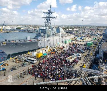 191127-N-NG710-1098  SAN DIEGO (Nov. 27, 2019) Friends and family members gather near the amphibious assault ship USS Boxer (LHD 4) as the ship moors at Naval Base San Diego. Boxer, part of the Boxer Amphibious Ready Group (ARG), is returning to its homeport of San Diego following a 7-month deployment to the 5th and 7th fleet area of operations. (U.S. Navy photo by Mass Communication Specialist 2nd Class Justin Daniel Rankin) - Stock Photo