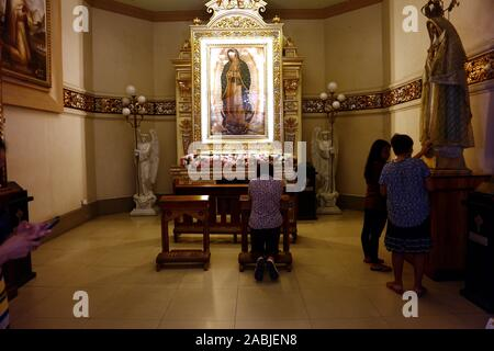 Antipolo City, Philippines – November 26, 2019: Catholic devotees pray to religious statues on an altar inside the Antipolo Cathedral or the Our Lady - Stock Photo