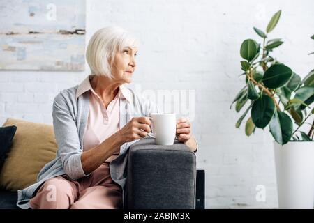 senior woman sitting on sofa and holding cup of tea in apartment - Stock Photo
