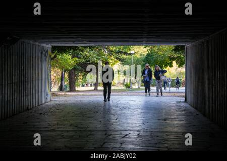 Varna, Bulgaria - People walking through a dark underpass with glowing end, underground passage, blurred people silhouettes - Stock Photo