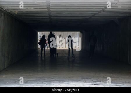 People walking through a dark underpass with glowing end, underground passage, blurred people silhouettes - Stock Photo