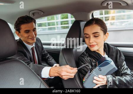 Businessman paying off with credit card in taxi - Stock Photo