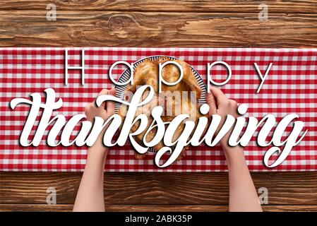 cropped view of woman holding roasted turkey on red plaid napkin on wooden table with happy thanksgiving illustration - Stock Photo