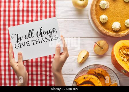 partial view of woman holding card with in all things give thanks illustration near pumpkin pie on wooden white table with apples and plaid red napkin - Stock Photo