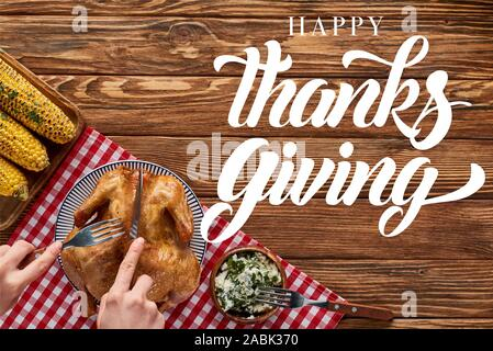 cropped view of woman cutting roasted turkey on red plaid napkin near grilled corn on wooden table with happy thanksgiving illustration - Stock Photo