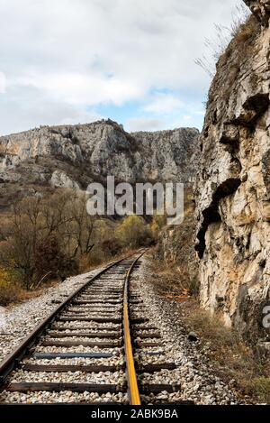 Old abandoned railway tracks in nature leading into the tunnel, traveling by train - Stock Photo