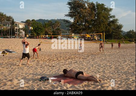 18.11.2019, Phuket, Thailand, Asia - A group of tourists plays volleyball at dusk on Karon Beach. - Stock Photo