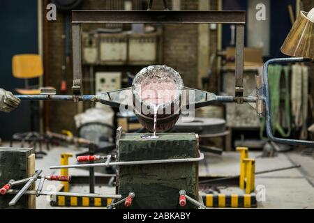 Metal sand casting technique pouring molten aluminum silver colored liquid into a mold in a industrial environment, workshop space - Stock Photo