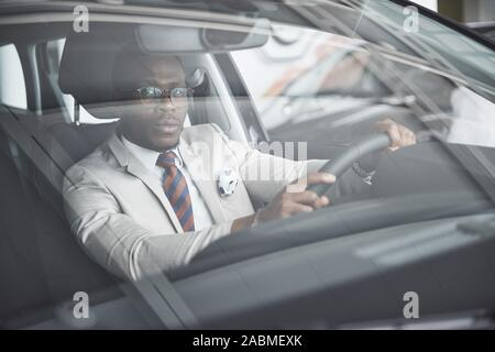 front view of Handsome african elegant serious business man drives a car - Stock Photo