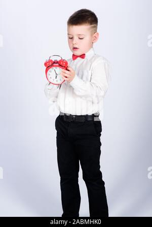 happy child with retro clock in bow tie. Party time. Businessman. Formal wear. Time management. Morning. little boy with alarm clock. Time to relax. tuxedo kid. Happy childhood. Good start of morning. - Stock Photo
