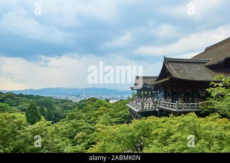 View of Kiyomizu Temple and Kyoto city in the distance, and many green trees in the foreground on a cloudy summer day in Kyoto, Japan. - Stock Photo