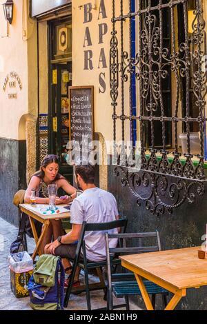 People enjoying outdoor sidewalk cafes in Santa Cruz or old Jewish Quarter of Seville Andulsia Spain