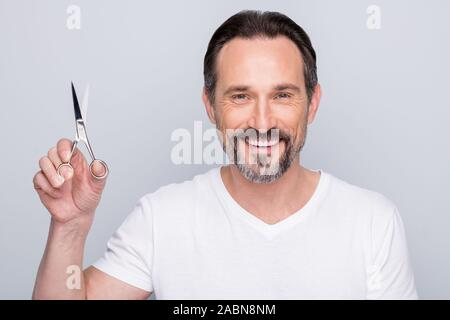 Closeup photo of mature guy metrosexual holding new cosmetology hairdo scissors advising cutting hair dresser professional salon wear white t-shirt - Stock Photo