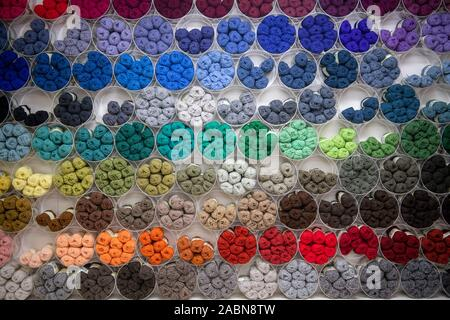Selection of different coloured wool yarn on display on a wall in Shetland wool shop - Stock Photo