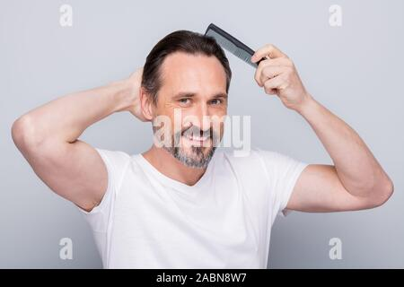 Closeup photo of macho cheerful mature guy holding hairbrush making hair styling after taking shower looking mirror bathroom wear white t-shirt - Stock Photo