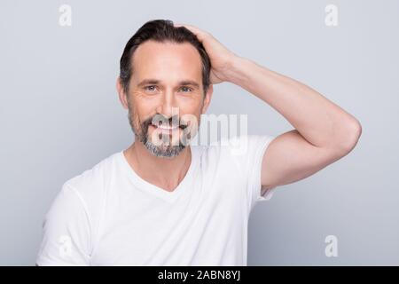 Closeup photo of handsome positive aged man looking mirror hands checking hairstyle after using new hair shampoo conditioner wear white t-shirt - Stock Photo