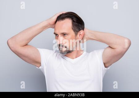 Closeup photo of handsome aged man seriously looking mirror hands checking hairstyle after visiting stylist salon wear white t-shirt isolated grey - Stock Photo