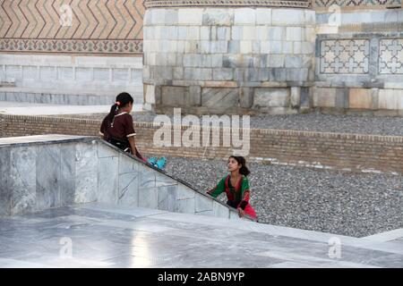 Young gypsy girls playing outside the Bibi-Khanym Mosque in Samarkand - Stock Photo