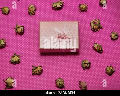 Photo of a beige flat lay gift box with bow among dried rose buds on a pink background top view - Stock Photo