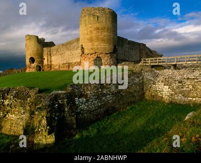 The south tower (centre) & west gatehouse (L) of the inner ward of Rhuddlan Castle, Denbighshire, Wales, UK, looking N over the stone-faced dry moat. - Stock Photo