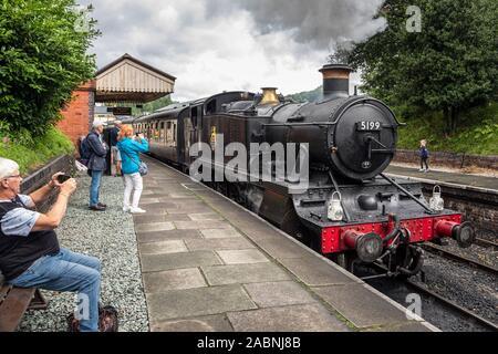 Tourists watching a steam engine leaving Llangollen station, Llangollen Railway, Denbighshire, Wales - Stock Photo