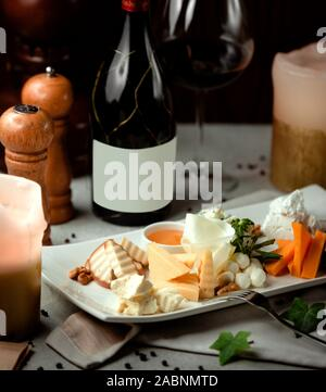 different types of sliced cheeses and a bottle of red wine - Stock Photo