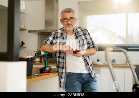 Mature handyman looking at camera leaning on ladder in modern kitchen - Stock Photo