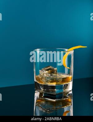 Old fashioned Whisky Cocktail with real ice on a blue background with reflection - Stock Photo