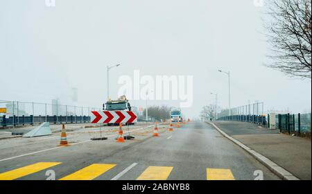 Strasbourg, France - Dec 21, 2016: Roadworks in France with half road closed construction trucks in background - Stock Photo