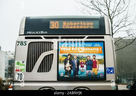 Strasbourg, France - Dec 21, 2016: Rear view of Heuliez Bus piublic transportation bus driving in city with destination Robertsau Chasseurs - Stock Photo