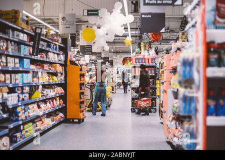 Strasbourg, France - Dec 21, 2016: Interior of large French Auchan supermarkets with worker preparing goods to be arranged on the shelves and customers shopping - Stock Photo