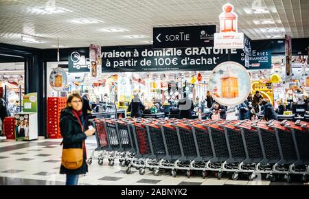 Strasbourg, France - Dec 21, 2016: Woman silhouette waiting near the shopping carts in the large French Auchan supermarket - Stock Photo