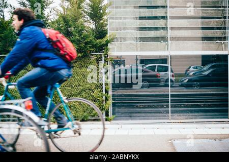Strasbourg, France - Dec 21, 2016: Side view of fast motion man on the bicycle and reflection of cars waiting in traffic jam - Stock Photo