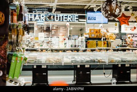 Strasbourg, France - Dec 21, 2016: Interior of large French Auchan supermarkets Charcuterie sign and multiple meat and cheese products in large fridge - Stock Photo