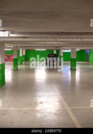 Strasbourg, France - Dec 21, 2016: Vertical image of black cabriolet convertible Volkswagen Beetle mini car parked in empty underground green wall parking - Stock Photo