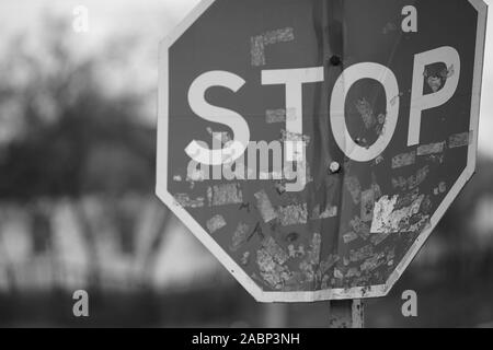 Old dirty bent road stop sign close-up, blurred rural house in the background. Black and white photo. - Stock Photo