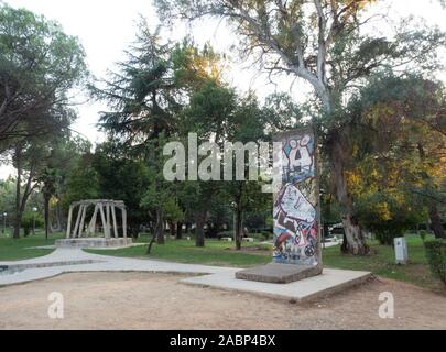 Tirana, Albania - September 29, 2019: Former Post-Block Checkpoint to elite residential neighborhood with portion of Berlin Wall and pillars from Spac - Stock Photo