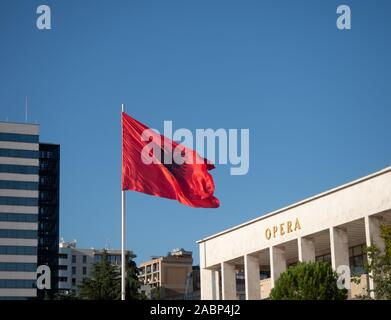 Tirana, Albania - September 29, 2019: Unfurled Albanian flag with a double-headed eagle in black against a red background. Part of the National Theatr - Stock Photo