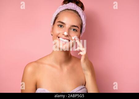 A girl with a bandage on her head and patches under her eyes stands on a pink background, puts white cream on her face, smiling. - Stock Photo
