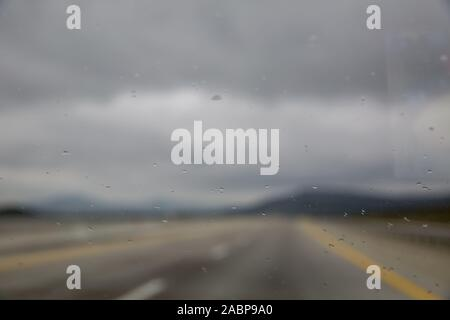 Rain drop on glass of the car road with fog or mist in green nature . Water drops on the glass in car . raindrops - Stock Photo
