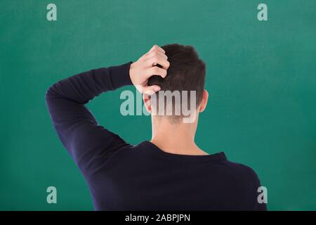 Rear View Of Young Man In Blue T-shirt Scratching His Head Against Green Background - Stock Photo